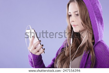 young woman with smart phone listening music. Teen stylish long hair girl in hood relaxing or learning language. Studio shot on violet. - stock photo