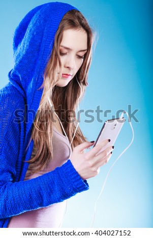 young woman with smart phone listening music. Teen stylish long hair girl in hood relaxing or learning language. Studio shot on gray. - stock photo