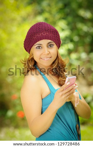 Young Woman with smartphone, green background - stock photo