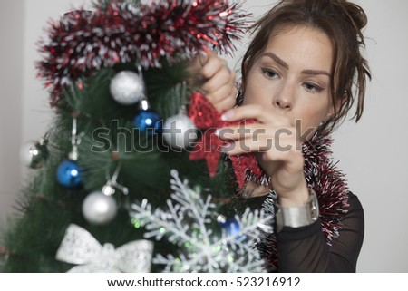 Young woman with smile  decorates a Christmas tree