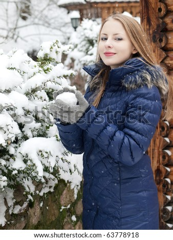 young woman with snowball in blue coat outdoor - stock photo