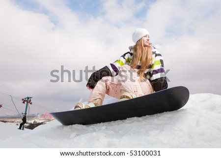 Young woman with snowboard sitting on the slope of hill - stock photo