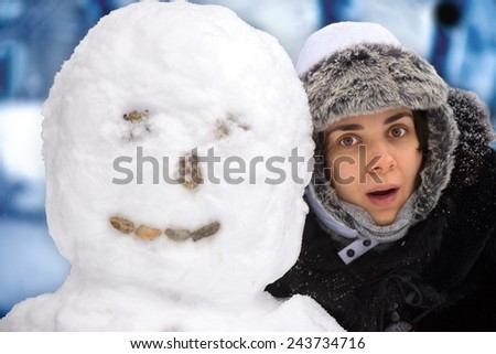 Young woman with snowman - stock photo