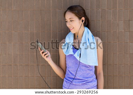 Young woman with sportwear and listen to music - stock photo