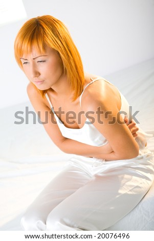 Young woman with stomachache sitting on bed. She's hugging her abdomen. - stock photo