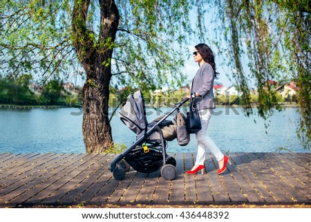 young woman with stroller on lake deck on city park. Happy mother walking child with pram - stock photo