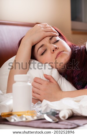 Young woman with strong flu lying in bed