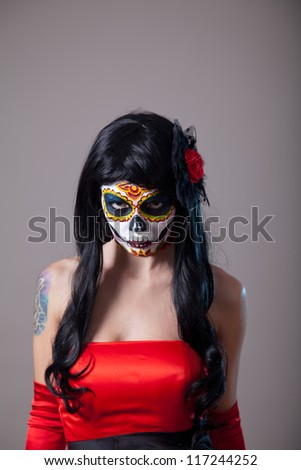Young woman with sugar skull Halloween make-up wearing red dress, the Day of the Dead - stock photo