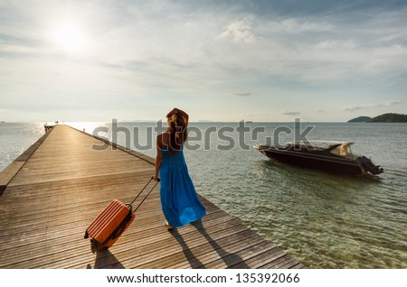 Young woman with suitcase on the pier.