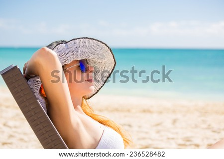 Young woman with sun hat enjoying the sea view sitting laying on a beach's chair close to the sea blue ocean. Travel tropical vacation paradise destination nature getaway freedom concept  - stock photo