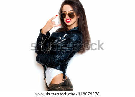Young woman with sunglasses giving the Rock and Roll sign.White background, not isolated.black leather jacket.Woman dancing and going crazy,fancy woman,classic aviator sunglasses,fashionista,red lips - stock photo