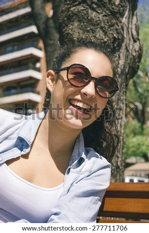 Young woman with sunglasses laughing - stock photo