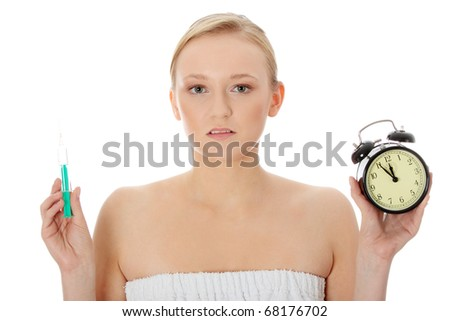 Young woman with syringe and clock, isolated - stock photo