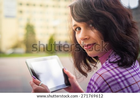 Young woman with Tablet reading from ebook - stock photo