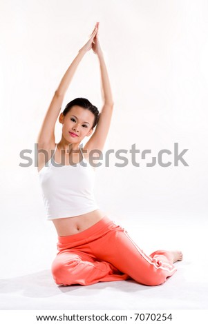 young woman with tank top and orange pants doing stretching exercise while smiling