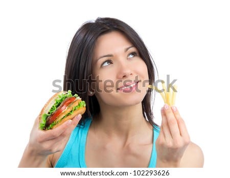 Young woman with tasty fast food unhealthy burger in hand  and french fries getting ready to eat isolated on a white background - stock photo