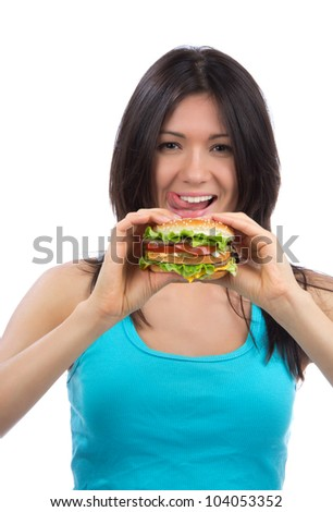 Young woman with tasty fast food unhealthy burger in hand hungry getting ready to eat isolated on a white background - stock photo
