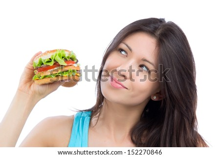 Young woman with tasty fast food unhealthy burger in hand to eat isolated on a white background - stock photo