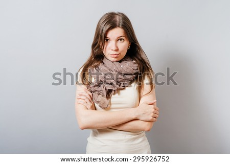 Young woman with the sour look crossed her arms. On a gray background. - stock photo