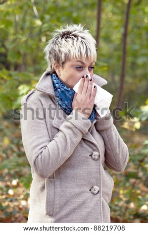 Young woman with tissue blowing her nose - stock photo