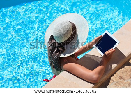 young woman with touch pad on vacation - stock photo