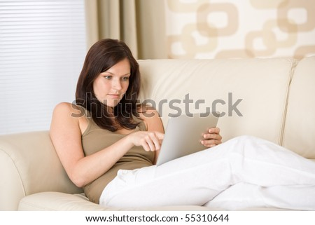Young woman with touch screen tablet computer in lounge - stock photo
