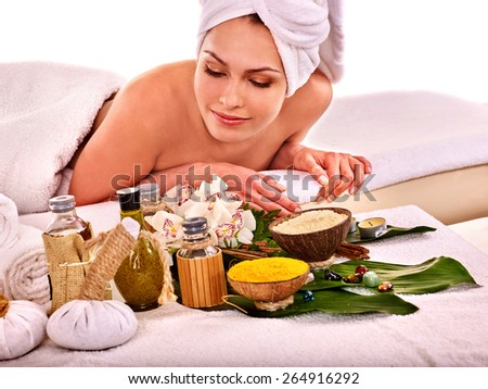 Young woman with towel on head getting spa treatment . Isolated. - stock photo