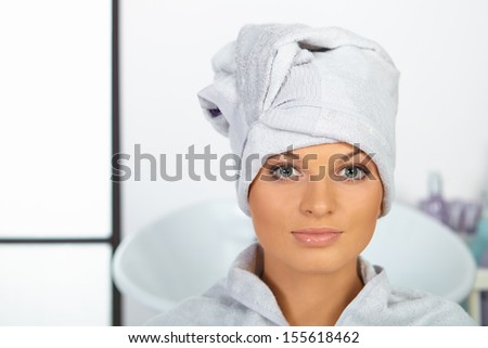 Young woman with towel on head sitting in hair salon.