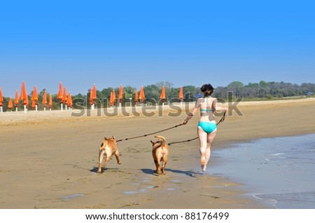 Young woman with two dogs running on the beach