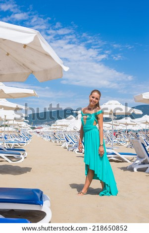 young woman with umbrella and sunbathing bad on a beach - stock photo