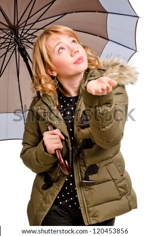 Young woman with umbrella checking if it rains - isolated on white - stock photo