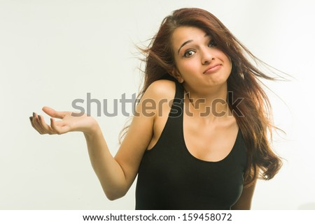 Young woman with uncertain expression posing in front of white background - stock photo