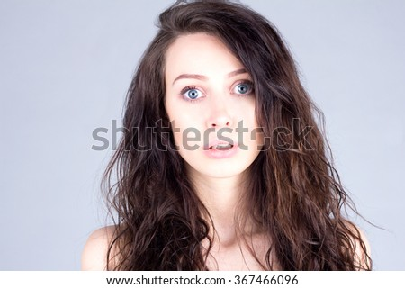 Young woman with very large eyes in surprise - stock photo