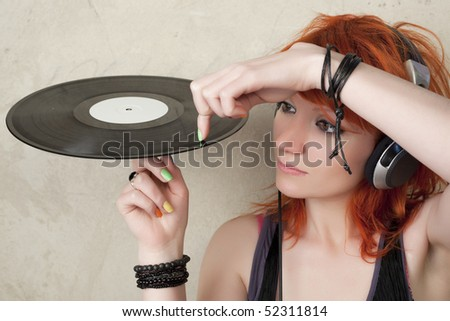 Young woman with vinyl and head phone mixing