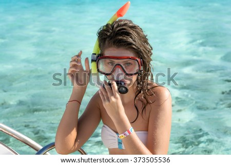 Young  woman with wet hair and with a snorkel and mask standing against turquoise sea water.  - stock photo