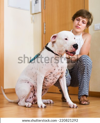 Young woman with white big dog on leash indoor. Focus on dog