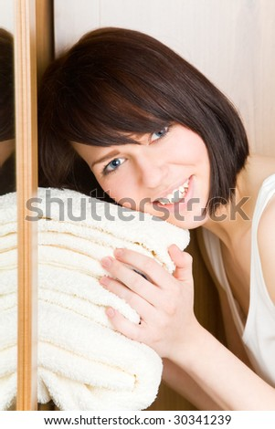 Young woman with white towels in her wardrobe - stock photo