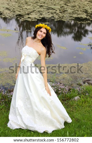 young woman with wreath of dandelions summer outdoor, beautiful bride has fun in summer park - stock photo