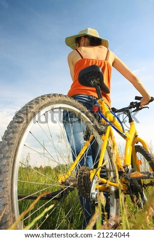 Young woman with yellow bicycle - stock photo