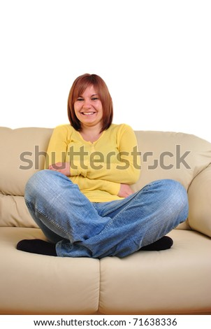 young woman with yellow shirt sits on a couch