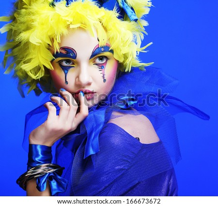 Young woman with yellow wig feather. Holiday theme. - stock photo