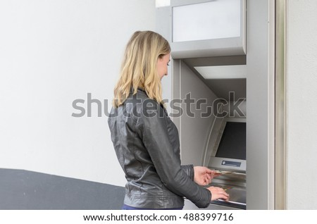 Young woman withdrawing money at an ATM standing with her back to the camera waiting for the machine to dispense the banknotes