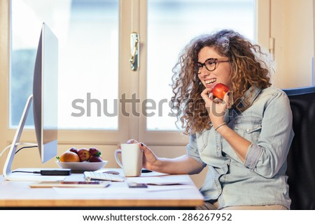 Young woman working at home or in a small office, vintage hipster clothing, curly hair. She is eating some fresh fruits, there is a cup of tea or coffee on the desk with some technological devices. - stock photo