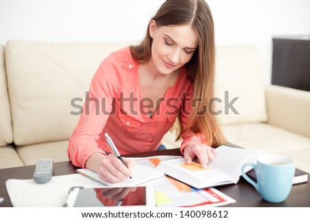 Young woman working at home. Sitting on couch.