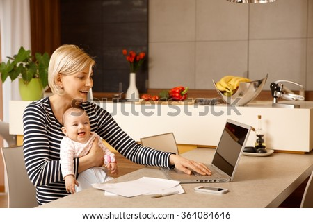 Young woman working at home with computer, holding baby girl in arms.