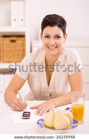 Young woman working at home, writing on paper, besides her breakfast on the table.