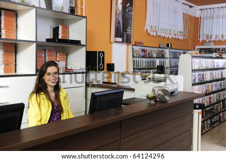 young woman working at the video rental store - stock photo