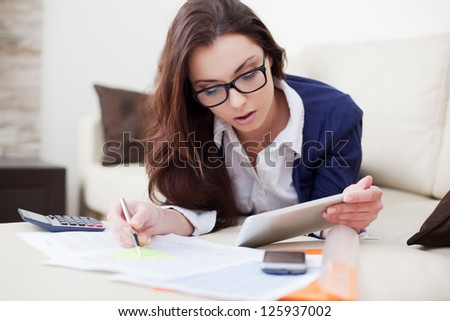 Young woman working from home using her digital tablet - stock photo