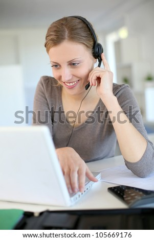 Young woman working from home with laptop and headset - stock photo