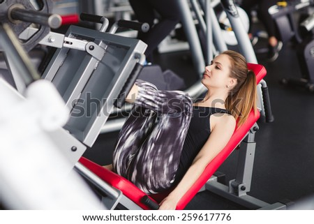 Young woman working her quads at machine press in the gym. Pretty Hispanic brunette exercising in a simulator in a gym - stock photo